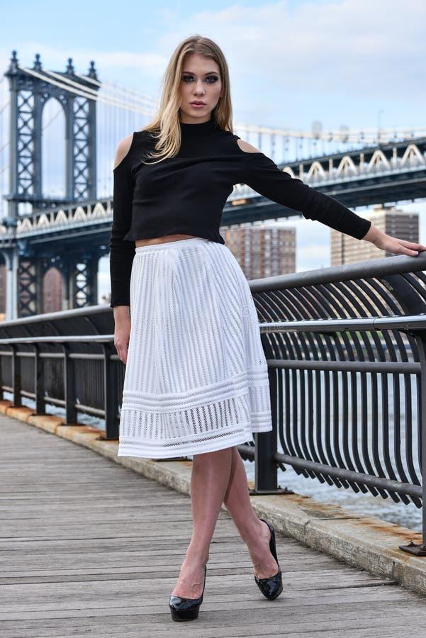Attraktives blondes Mode-Modell, das recht auf dem Pier mit Manhattan-Brücke auf dem Hintergrund aufwirft stockbild