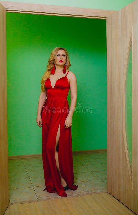 Attraktives blondes Modell im roten Kleid, das in einem Studio aufwirft lizenzfreie stockfotos