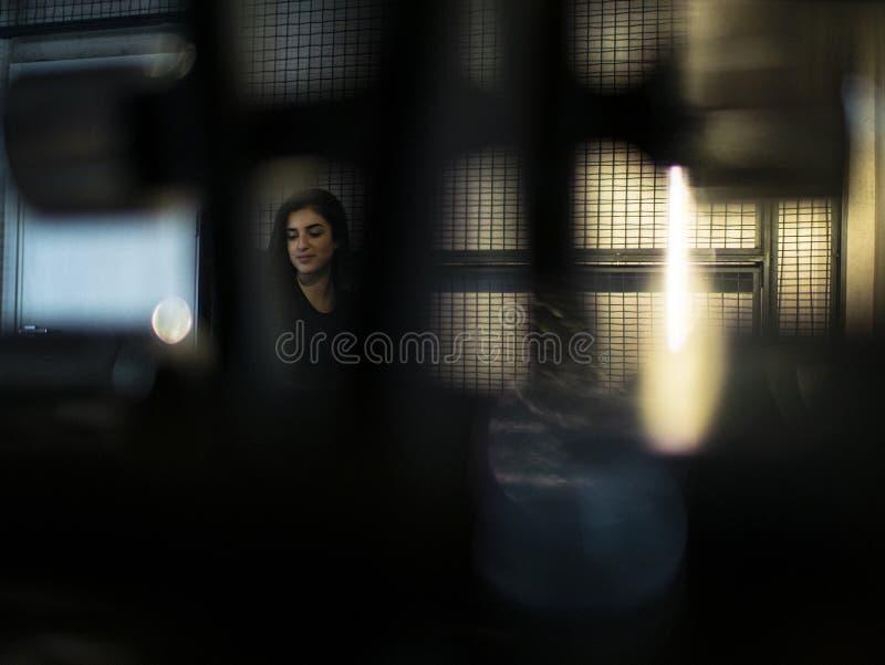 Attraktives brunette Mädchen in einer schwarzen Spitze und in den Gamaschen sitzt auf einer Bank in einer sortierenden Halle auf  lizenzfreie stockbilder