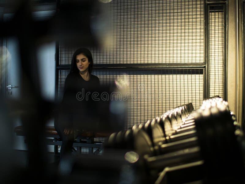 Attraktives brunette Mädchen in einer schwarzen Spitze und in den Gamaschen sitzt auf einer Bank in einer sortierenden Halle auf  stockfotografie