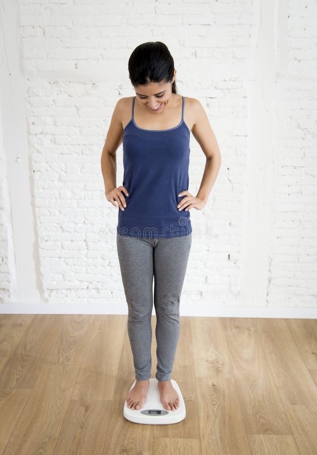Attraktives dünnes lateinisches Frauen- oder Jugendlichmädchen, das Gewicht auf dem Skalalächeln glücklich und erfüllt überprüft lizenzfreie stockbilder