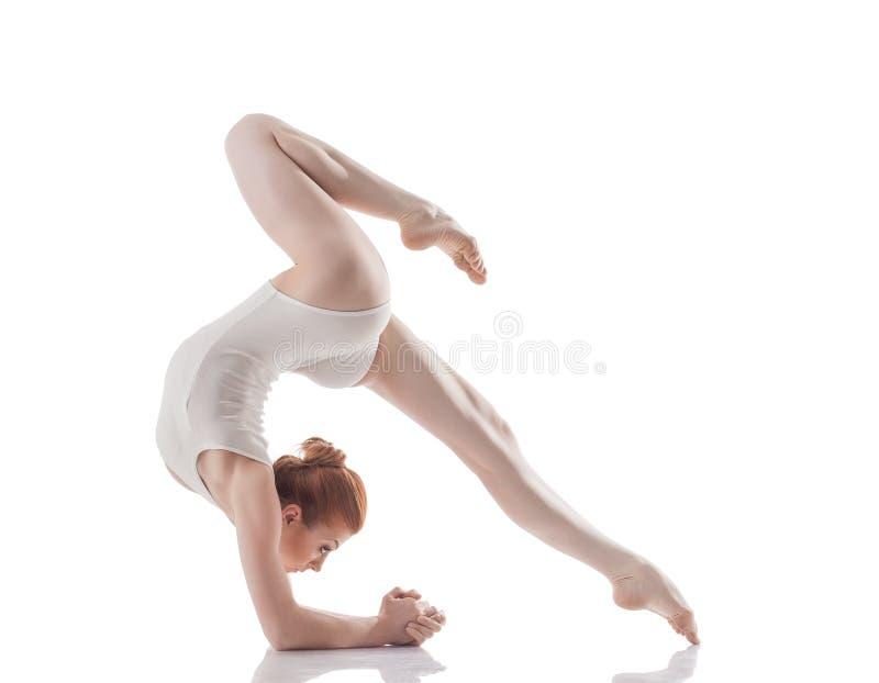Attraktives dünnes Mädchen, das akrobatischen Trick tut lizenzfreie stockbilder