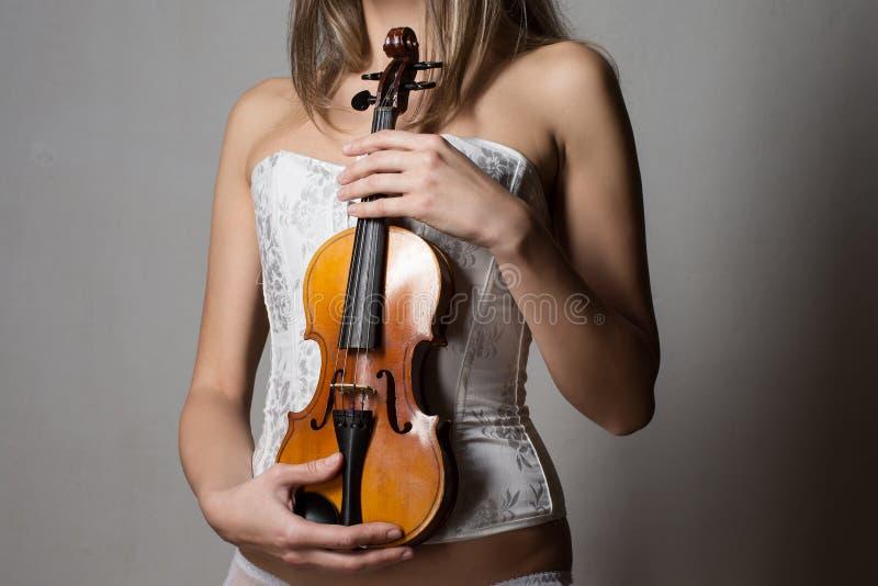 Attraktives dünnes Mädchen im weißen Korsett, das eine Violine hält stockfoto