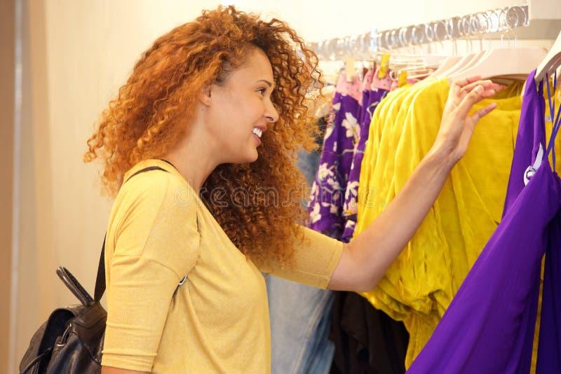 Attraktives Einkaufen der jungen Frau für Kleidung im Speicher stockfoto