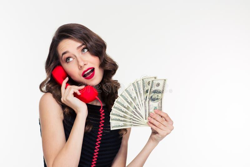 Attraktives frohes gelocktes weibliches haltenes Geld und Unterhaltung am Telefon stockfoto