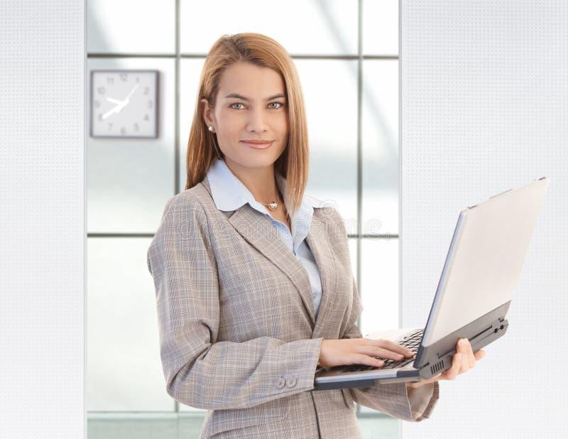 Attraktives Geschäftsfrauholding-Laptoplächeln stockfoto