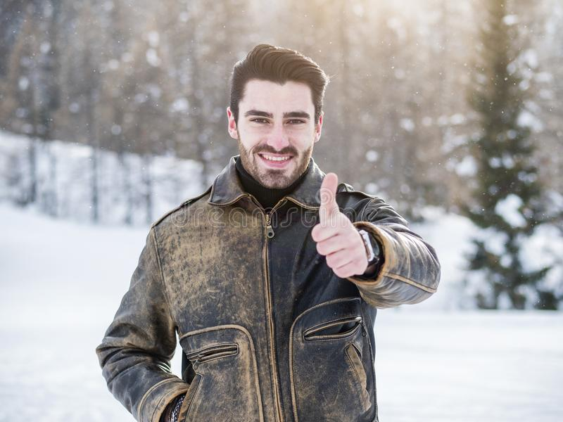 Attraktives glückliches Lächeln des jungen Mannes, Daumen herauf Zeichen tuend stockfotografie