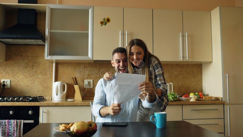 Attraktives glückliches Paar erhalten Ausbreitenbrief der guten Nachrichten in der Küche, während zu Hause frühstücken Sie stockbild