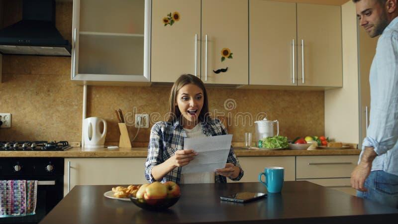 Attraktives glückliches Paar erhalten Ausbreitenbrief der guten Nachrichten in der Küche, während zu Hause frühstücken Sie stockfotos