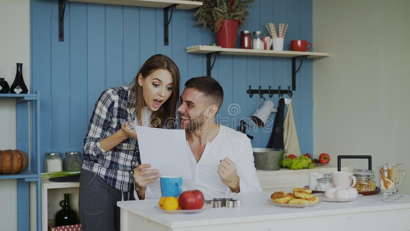 Attraktives glückliches Paar erhalten Ausbreitenbrief der guten Nachrichten in der Küche, während zu Hause frühstücken Sie stockfotografie