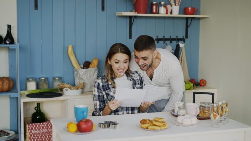 Attraktives glückliches Paar erhalten Ausbreitenbrief der guten Nachrichten in der Küche, während zu Hause frühstücken Sie stockbilder