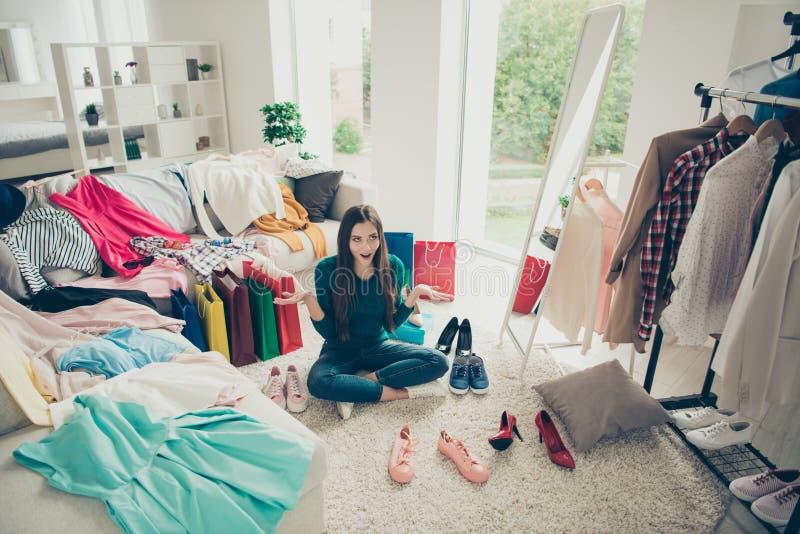 Attraktives hübsches nettes lustiges nettes heitres Mädchen, das auf Boden unter der unterschiedlichen Kleidung macht Wahl was, s stockfotos