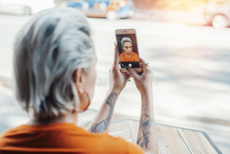 Attraktives Hippie-Mädchen im orange T-Shirt, das selfie am Café durch ihr Telefon macht stockbild