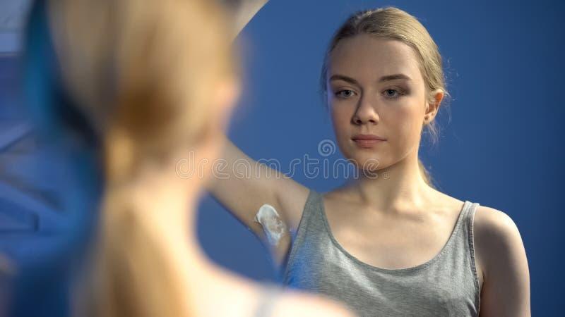 Attraktives jugendlich Mädchen, das Achselhöhle vor persönlicher Hygiene des Badezimmerspiegels rasiert stockfotos