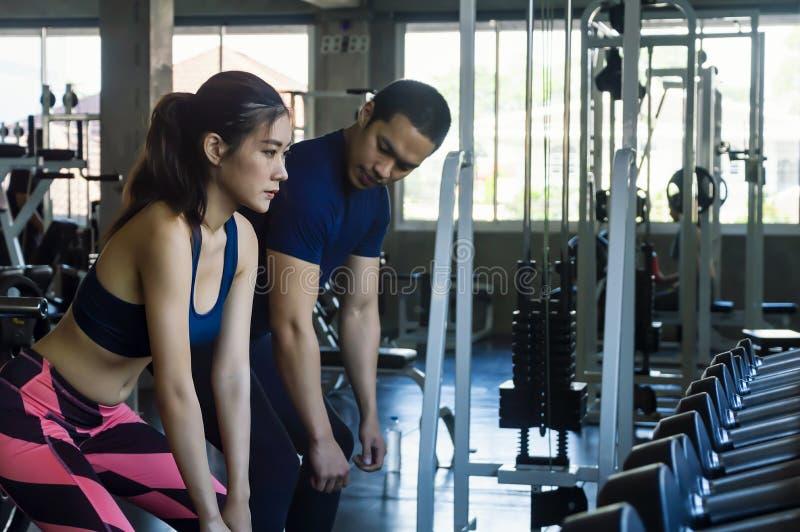 Attraktives junges athletisches Mädchen, das Hocke in der modernen Turnhalle tut lizenzfreie stockbilder