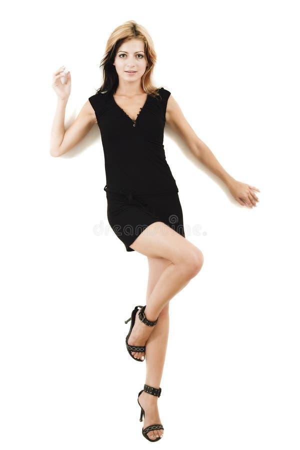 Attraktives junges Baumuster, das in einem netten schwarzen Kleid aufwirft stockbilder