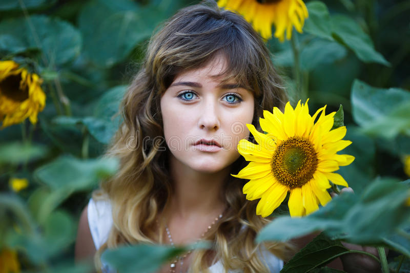Attraktives junges Mädchen auf dem Gebiet von Sonnenblumen lizenzfreies stockfoto