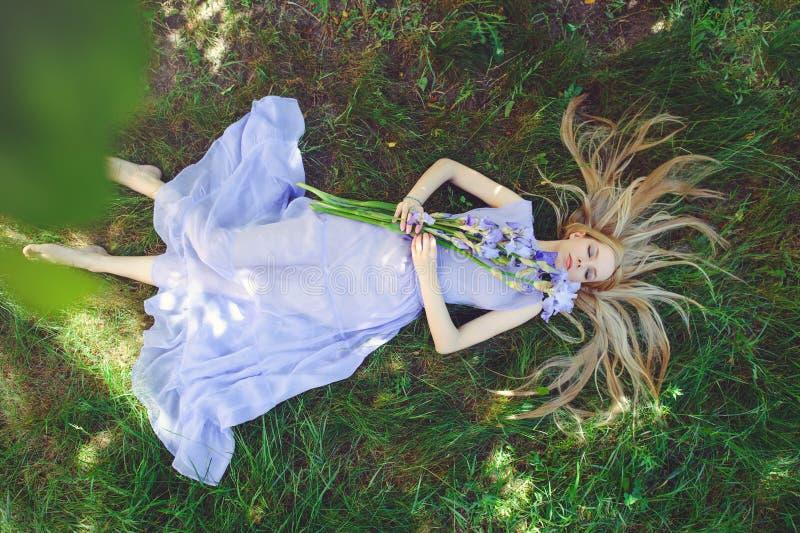 Attraktives junges Mädchen mit dem blonden Haar und natürlichen dem Make-up, die blaue purpurrote Iris riecht, blüht auf Gras dra stockfotografie