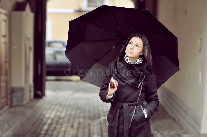 Attraktives junges Mädchen mit ubrella in einer alten Stadt stockfotografie