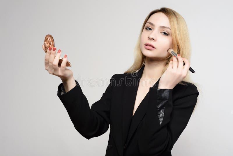 Attraktives junges Mädchen tut Maskenbildner selbst mejk, das Blicke eines Spiegels an der Kamera hält stockbild
