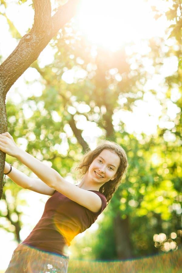 Attraktives junges Mädchen wirft am Baum auf stockfoto