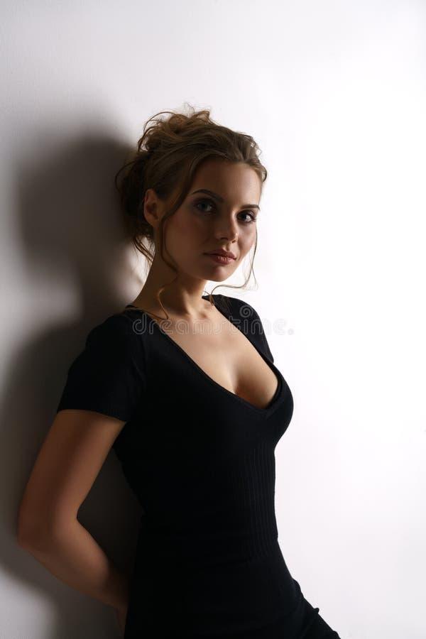Attraktives junges Modell im schwarzen hautengen Kleid stockfotografie