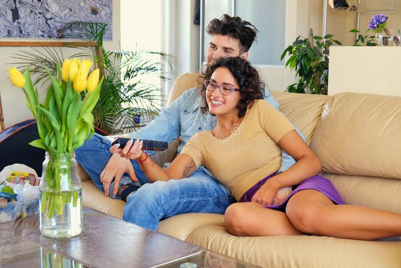 Attraktives junges Paar sitzt auf einer Couch mit einem Laptop auf einer Tabelle in einem Wohnzimmer lizenzfreie stockbilder