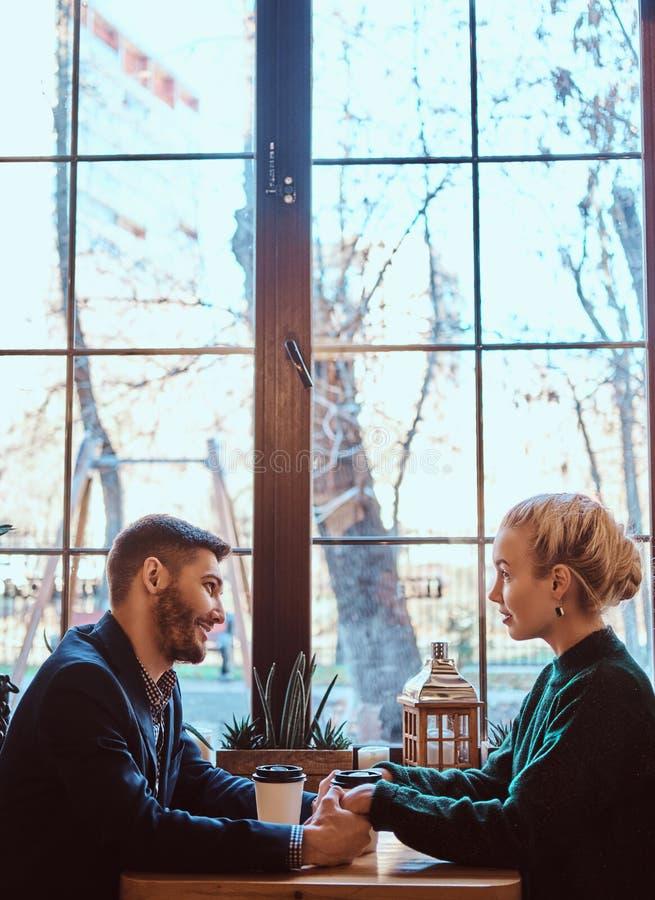Attraktives junges Paarhändchenhalten, einander betrachtend und sprechen beim Sitzen im Restaurant lizenzfreies stockbild