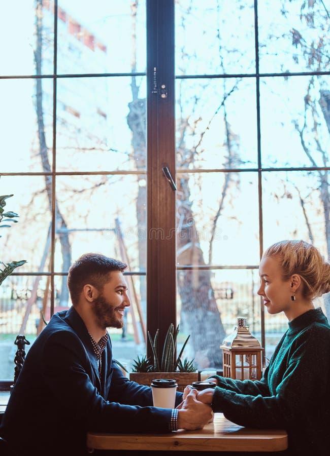Attraktives junges Paarhändchenhalten, einander betrachtend und sprechen beim Sitzen im Restaurant lizenzfreie stockbilder