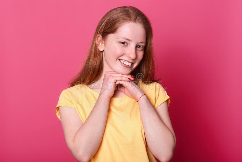 Attraktives junges süßes nettes Mädchen mit Lächeln auf ihrem Gesicht, Arme nahe Kinn halten Rote behaarte Dame mit roten Manikür lizenzfreies stockbild