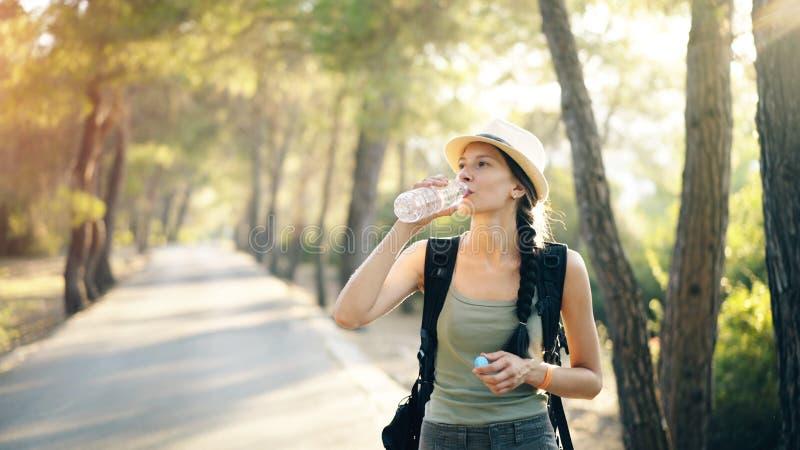 Attraktives junges touristisches Mädchen, das durch Trinkwasser nach Wandererreise erneuert stockfoto