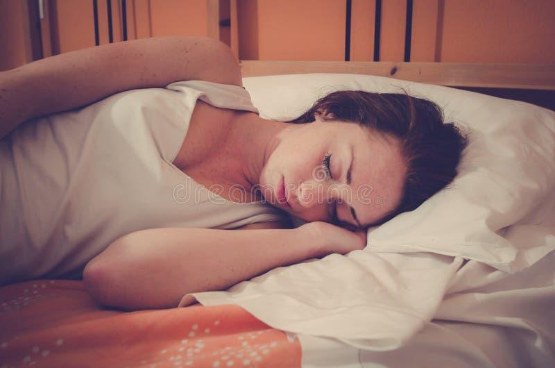 Attraktives kaukasisches Mädchen, das auf dem Bett schläft stockfotos