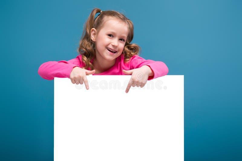 Attraktives kleines nettes Mädchen im rosa Hemd mit Affen und blaue Hose hält leeres Plakat stockfotos