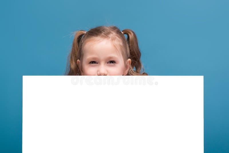 Attraktives kleines nettes Mädchen im rosa Hemd mit Affen und blaue Hose hält leeres Plakat stockfoto