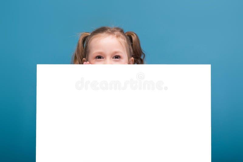 Attraktives kleines nettes Mädchen im rosa Hemd mit Affen und blaue Hose hält leeres Plakat lizenzfreie stockfotos
