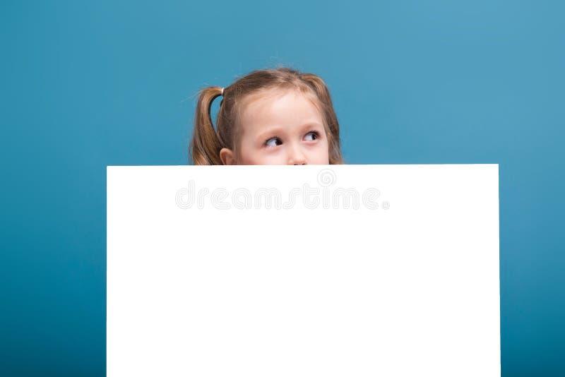 Attraktives kleines nettes Mädchen im rosa Hemd mit Affen und blaue Hose hält leeres Plakat stockbilder