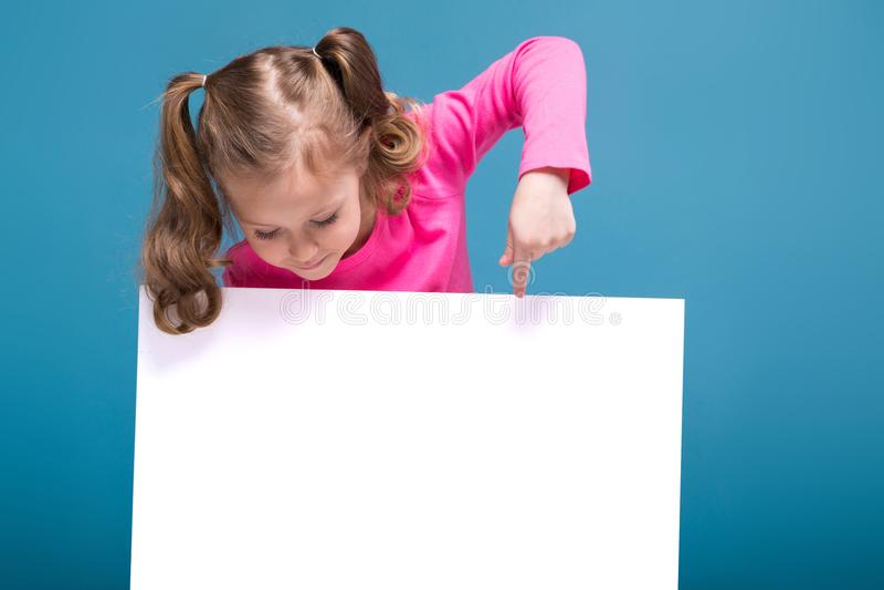 Attraktives kleines nettes Mädchen im rosa Hemd mit Affen und blaue Hose hält leeres Plakat lizenzfreie stockfotografie