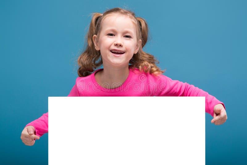 Attraktives kleines nettes Mädchen im rosa Hemd mit Affen und blaue Hose hält leeres Plakat lizenzfreies stockbild