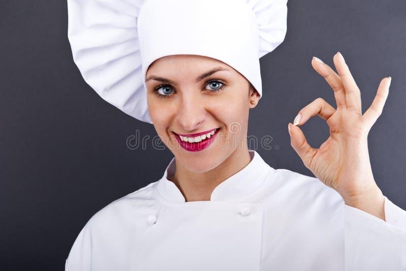 Attraktives Kochfrauenvertretungs-O.K. und -lächeln stockfoto