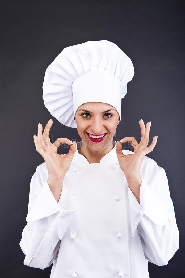 Attraktives Kochfrauenvertretungs-O.K. und -lächeln stockfotografie