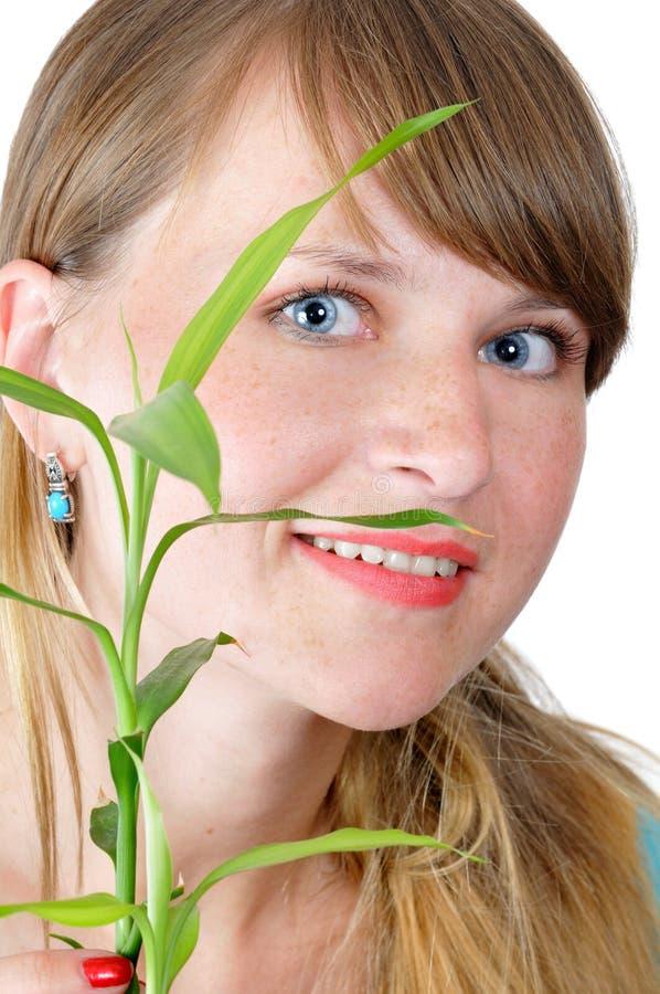 Attraktives lächelndes Mädchen mit einem Bambus stockfotos
