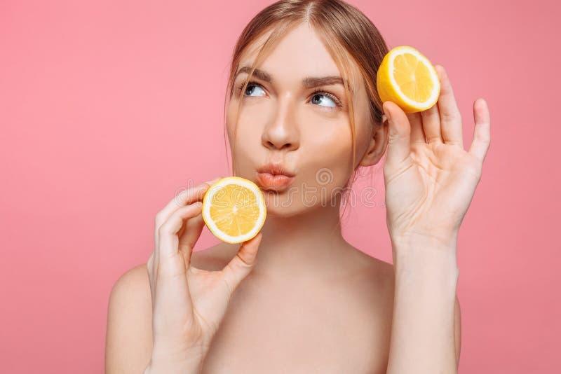 Attraktives lächelndes Mädchen mit sauberer Haut und Zitrone auf einem rosa Hintergrund stockbilder