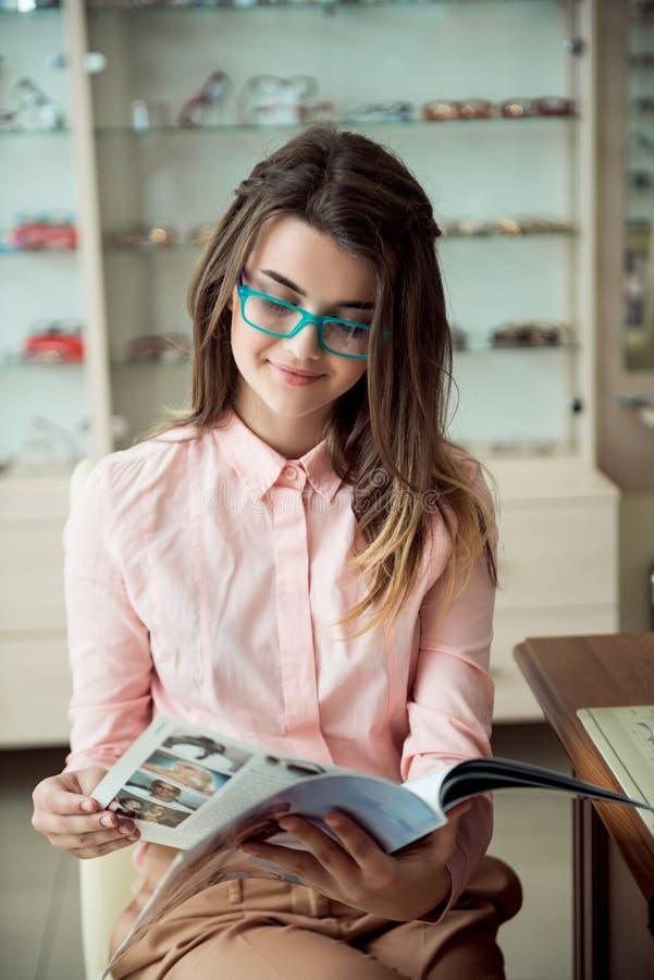 Attraktives Mädchen auf Verabredung im Ophthalmologebüro Porträt des europäischen jungen Brunettekunden, der in den Gläsern sitzt stockbilder