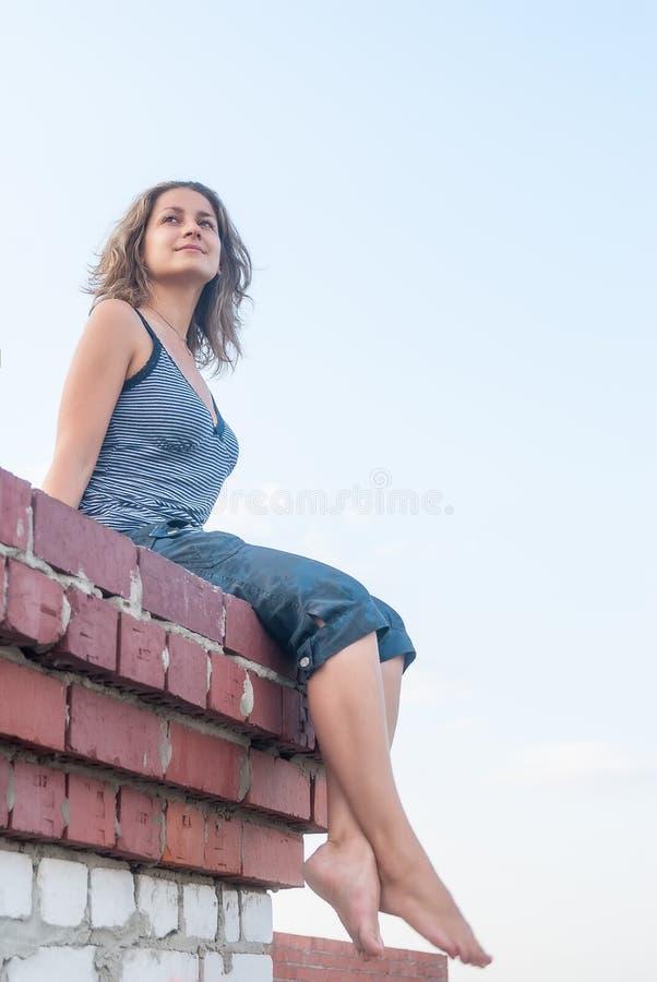 Attraktives Mädchen, das auf Dach sitzt lizenzfreie stockfotografie