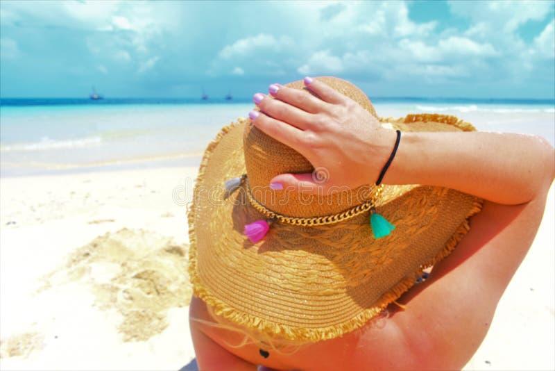 Attraktives Mädchen, das auf dem Paradiesstrand, ihren bunten Strohhut halten ein Sonnenbad nimmt und sich entspannt lizenzfreies stockbild