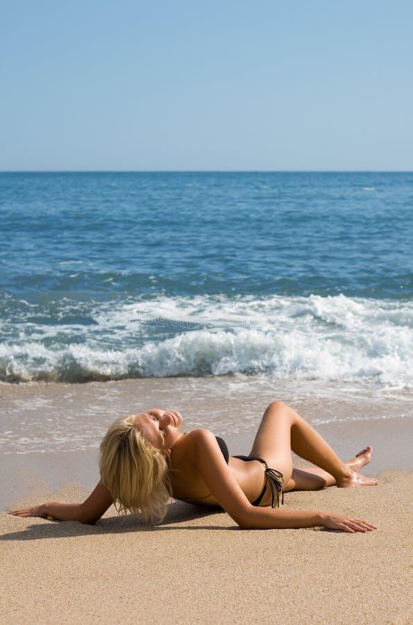 Attraktives Mädchen, das auf dem Strand durch das Meer sich entspannt. stockbild