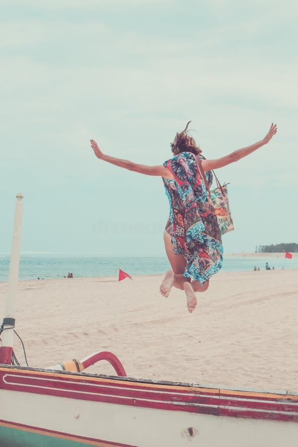Attraktives Mädchen, das auf den Strand hat Spaß, Sommerferien-Feiertag Lebensstil springt Glückliche Frauen, die Freiheit auf We lizenzfreie stockfotografie