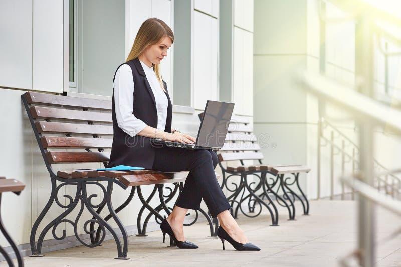 Attraktives Mädchen, das auf einer Bank nahe einem Geschäftsgebäude mit einem Laptop sitzt lizenzfreie stockbilder
