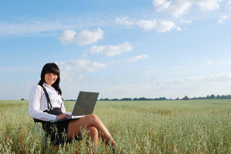 Attraktives Mädchen, das an Computer in der Natur arbeitet stockfotografie