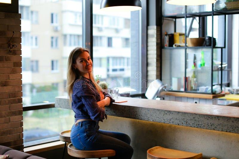 Attraktives Mädchen, das in der Stange am Café und an tragenden Jeans sitzt stockfotos